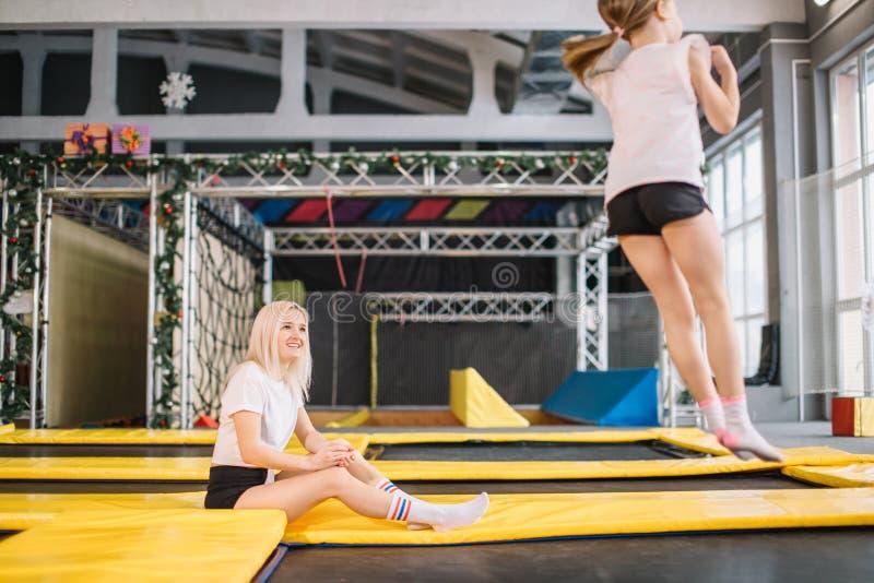 Dotter som studsar på trampolinen medan moderklocka för säkerhet royaltyfria bilder