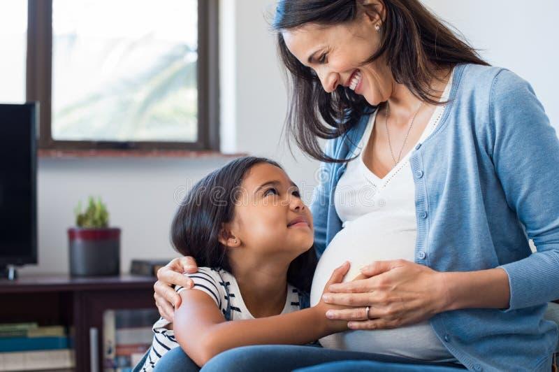 Dotter som trycker på buken av hennes gravida moder royaltyfria foton