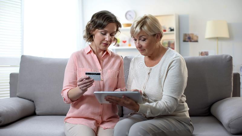 Dotter som undervisar den mogna modern som använder minnestavlan som skriver kortnummer, online-bankrörelsen royaltyfria foton