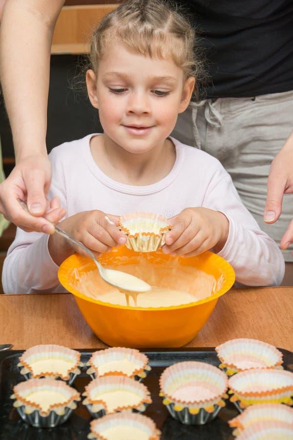 Dotterhåll gjuter för kakan, medan min moder drar degen från bunken royaltyfri foto