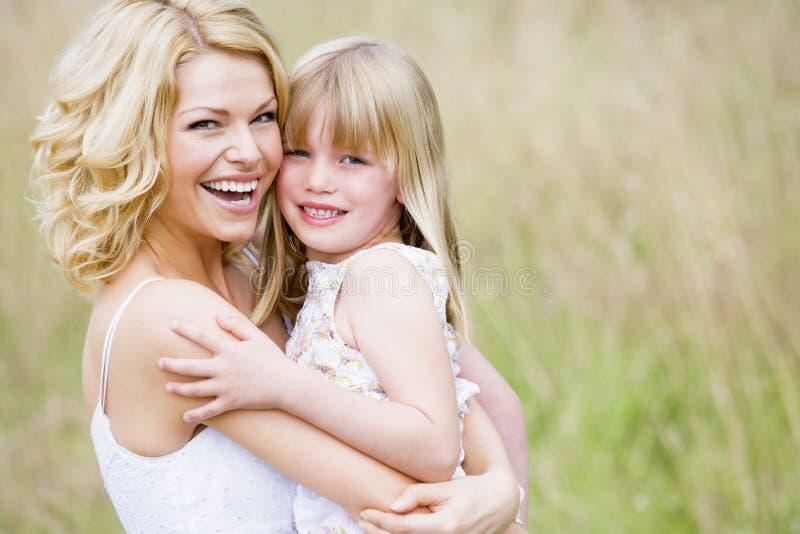 dotterholdingmoder som ler utomhus royaltyfri fotografi