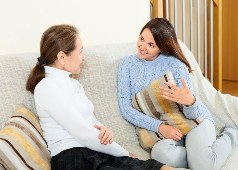 Dottern berättar något till hennes moder på soffan royaltyfri foto