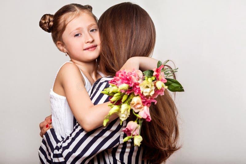 Dottern ger hennes moder blommor i studion, lycklig moder` s arkivbilder