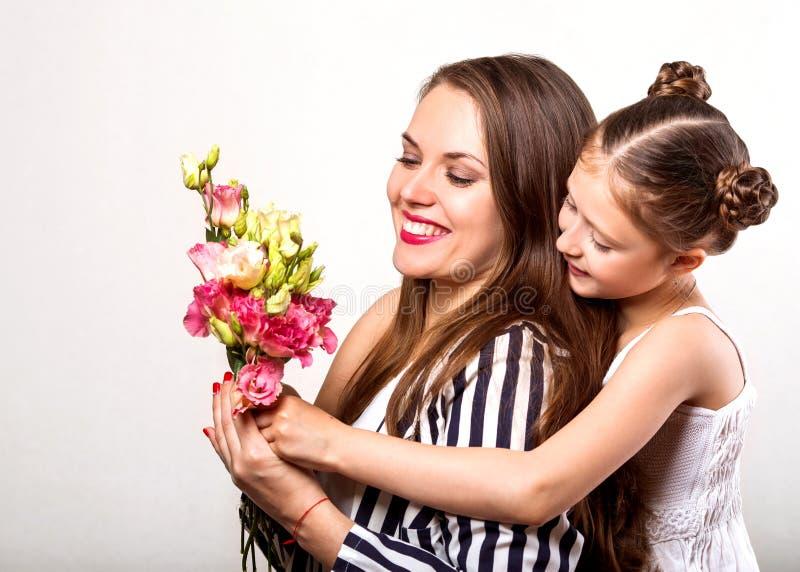 Dottern ger hennes moder blommor i studion, lycklig moder` s royaltyfria foton
