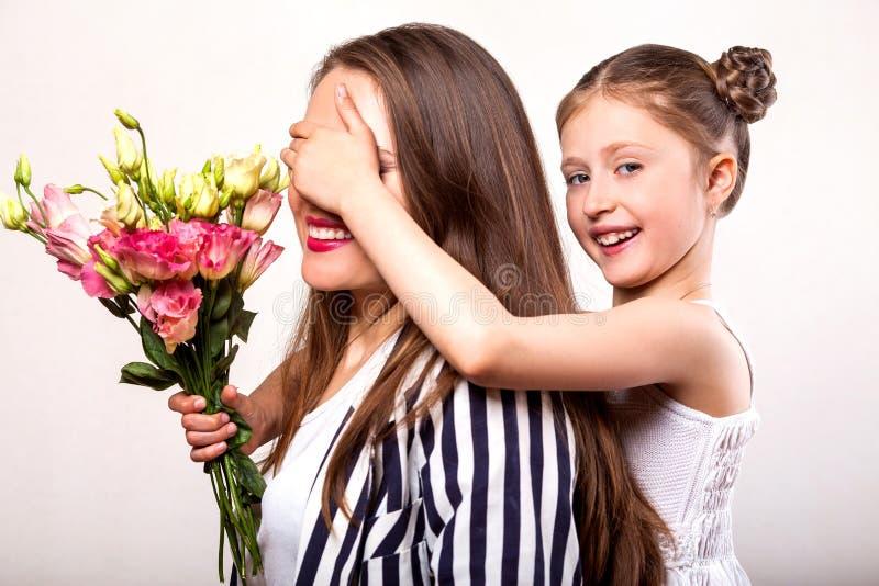 Dottern ger hennes moder blommor i studion, lycklig moder` s arkivfoto
