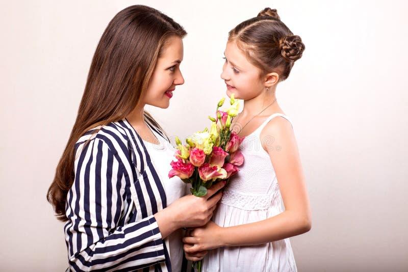 Dottern ger hennes moder blommor i studion, lycklig moder` s royaltyfria bilder