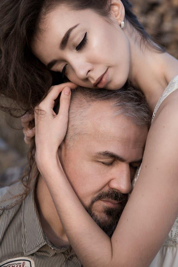 Dottern kramar fadern för huvud som de är kopplade av och lugna royaltyfri foto