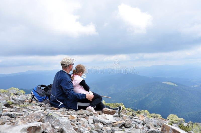 Dottern och fadern tycker om överst av berget, beundrar landskap royaltyfria foton