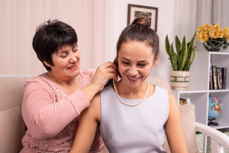Dottern och hennes moder som tillsammans spenderar tid Mamman ger hennes dotter pärlapärlor royaltyfria foton