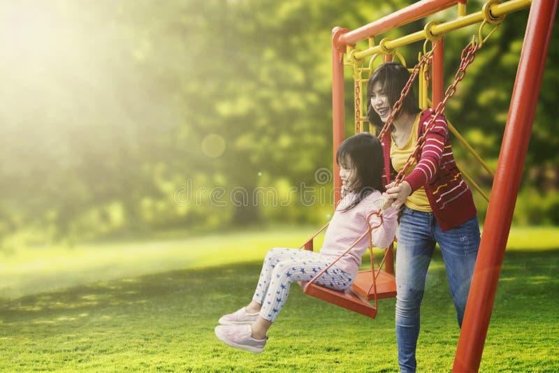 Dottern och modern som spelar gunga parkerar in royaltyfria bilder