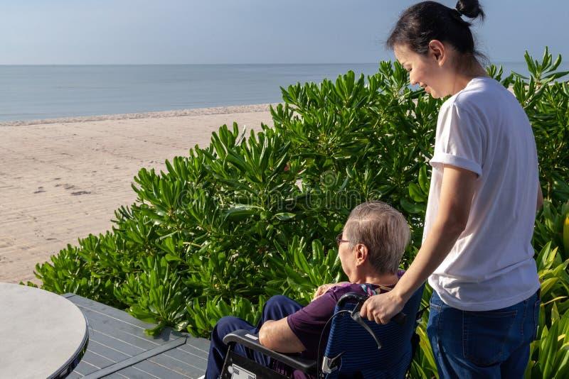 Dottern skjuter hjul-stolen framåtriktat för hennes moder framme av stranden arkivbild