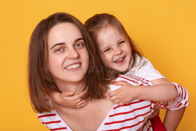Dottern som kramar modern från tillbaka tillgiven kvinna med toothy leende, rymmer det lyckliga lilla barnet, ungen som omfamnar  royaltyfria bilder