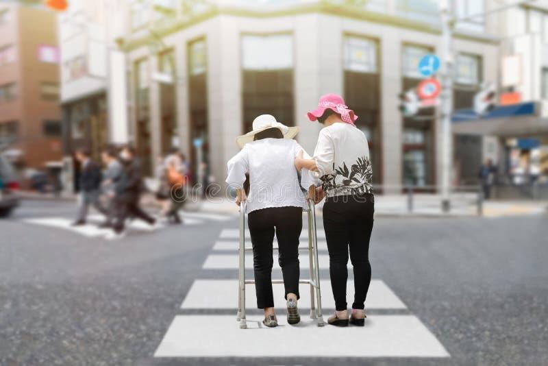 Dottern tar omsorg den äldre kvinnan som går över gatan arkivbild