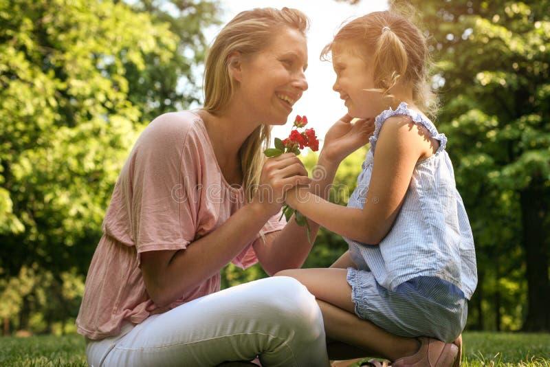 Dottern valde en blomma till hans moder arkivfoto