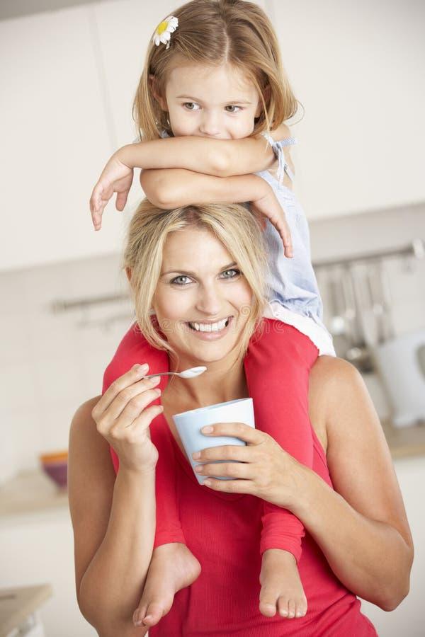 Dottersammanträde på skuldrastundmoder äter yoghurt royaltyfria bilder