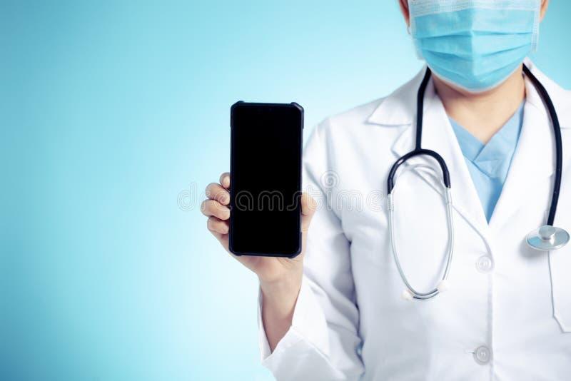 Dottore con stetoscopio e smartphone in mano per i concetti di esame medico immagini stock