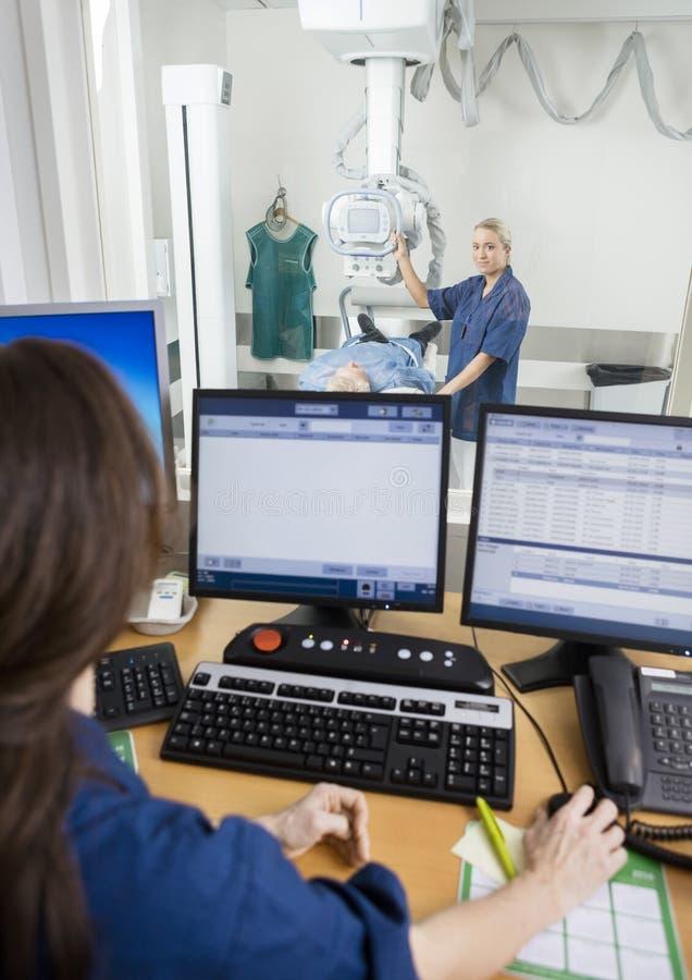 Dottore i raggi x del ` s di Taking Patient mentre collega che per mezzo del computer al De fotografie stock