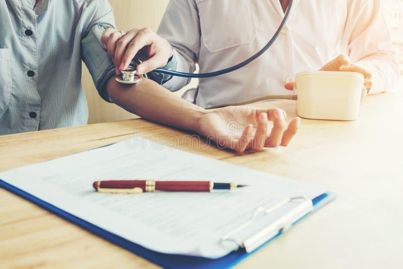 Dottore il paziente arterioso della donna di pressione sanguigna di Measuring sul braccio lui fotografia stock