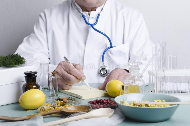 Dottore seduto al tavolo Molti ingredienti per la medicina alternativa Fragole secche, erbe aromatiche, limoni e diverse porzioni fotografia stock libera da diritti