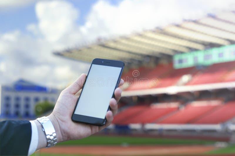 Dotyka ekran telefon komórkowy w ręce biznesmen przeciw tłu stadion futbolowy, Fotografia dla egzaminu próbnego Up obraz royalty free