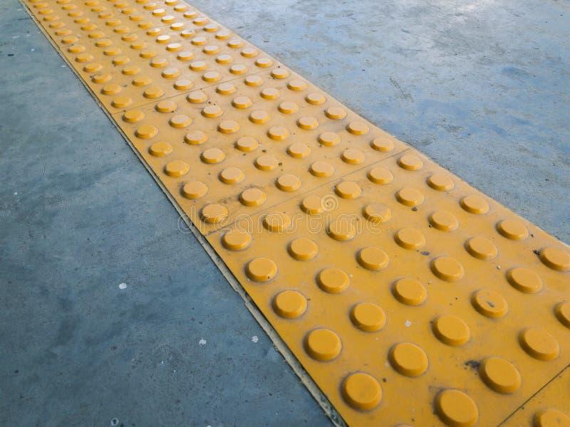 Dotykowy brukowanie lub Tenji blok na ziemi powierzchni jako przewodnictwo Pomagać Pedestrians które Wzrokowo Uszkadzali lub Wykr fotografia stock