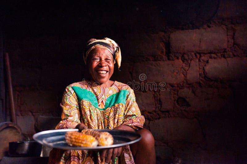 Douala Camerun - 6 agosto 2018: primo piano di signora africana anziana nella sua cucina domestica rurale con il vestito tradizio immagine stock libera da diritti