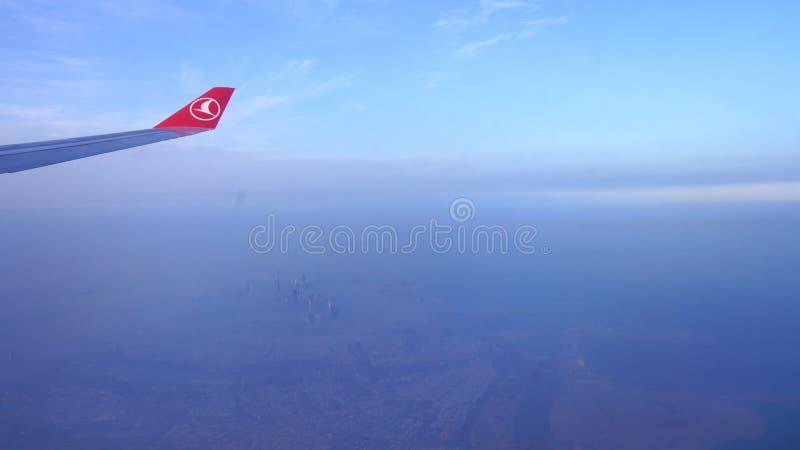 DOUBAI, VERENIGDE ARABISCHE EMIRATEN - 30 MAART, 2014: Een vleugel en venstermening uit een Turkish Airlines-vliegtuig met ochten royalty-vrije stock afbeeldingen