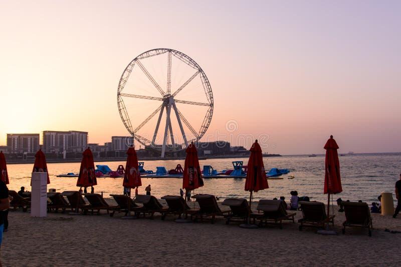 Doubai, Verenigde Arabische Emiraten - 8 Maart, 2018: Sunbeds en de romantische zonsondergang bij JBR, Jumeira-het strand van de  stock afbeelding