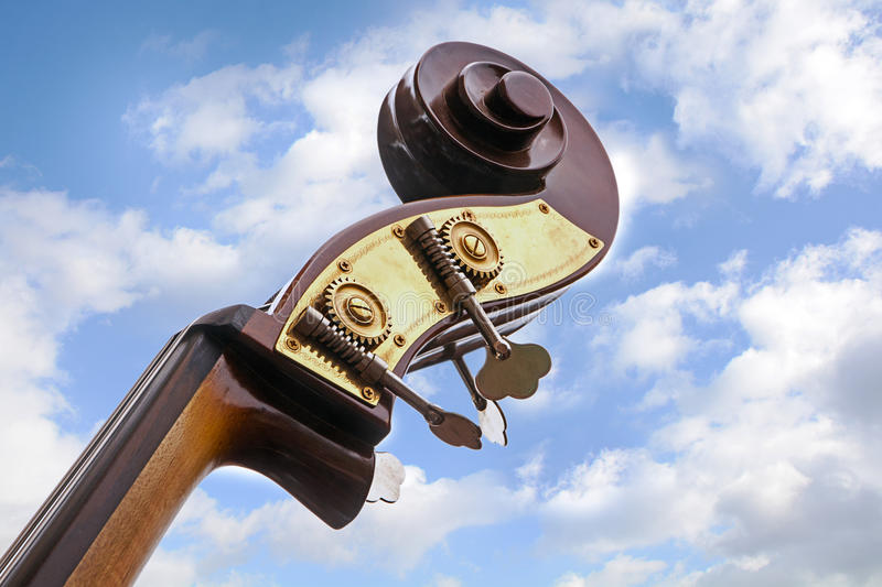 Double bass, detail of the music instrument neck, head with tu. Ning pegs and scroll against a blue sky with clouds, view from below, copy space royalty free stock images
