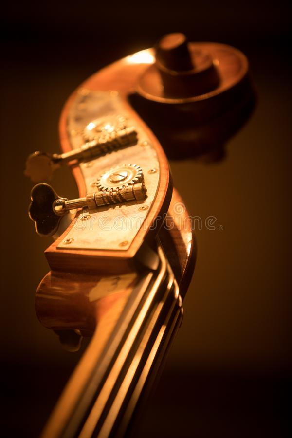 Double bass scroll and tuning pegs. Close up shot of a double bass scroll and tuning pegs stock photos