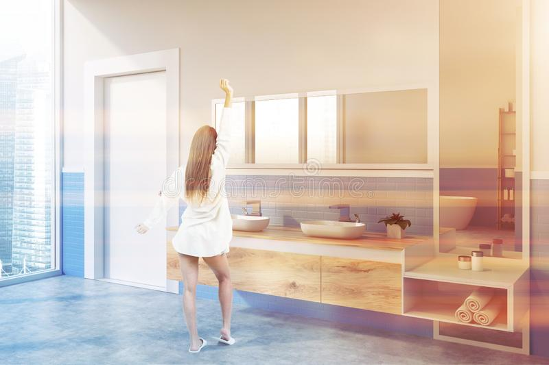 Double bathroom sink and door, woman. Woman in corner of modern bathroom with white and blue walls, concrete floor, double sink standing on wooden countertop stock photography