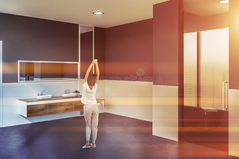 Double bathroom sink and shower, woman. Woman in corner of bathroom with white and gray walls, concrete floor, double sink standing on wooden countertop with stock photos