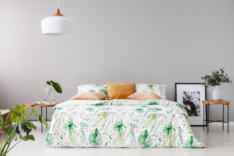 Double bed with floral duvet and peach colored pillow between two wooden nightstands with flowers in vases on it stock images