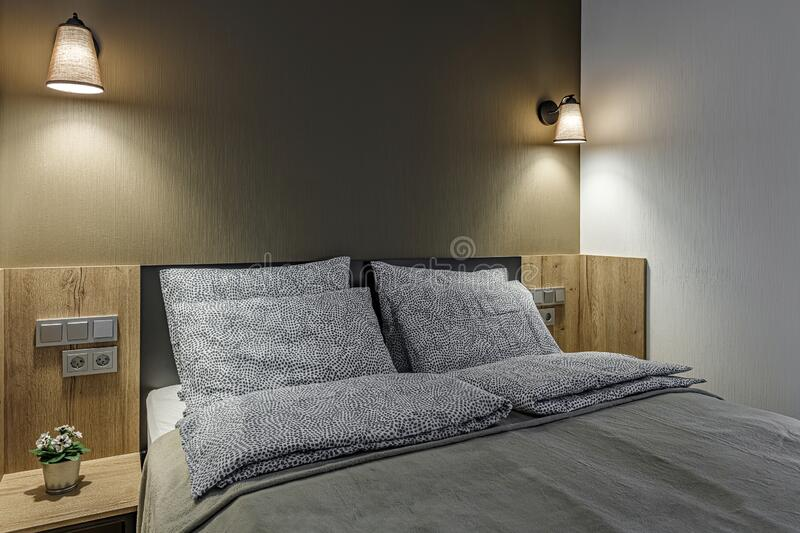 Double bed lamp and modern pillows in interior stock photography