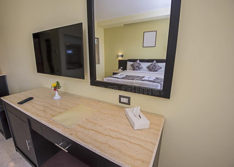 Double bed in a luxury suite of a hotel room. Double bed and dressing table in suite of a luxury hotel room with mirror reflection stock photo