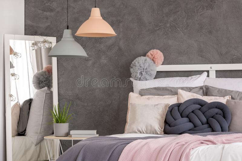 Double bed and mirror. Double bed covered with pillows standing next to a white mirror in a bedroom interior stock photos
