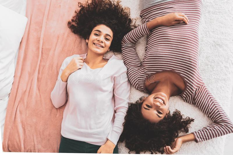 Smiling good-looking friends lying on double bed royalty free stock images