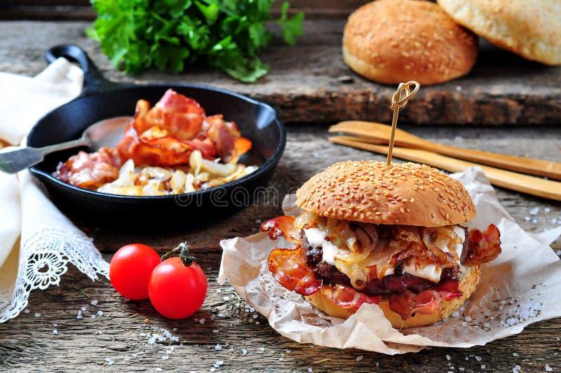 Double boeuf fait maison juteux d'hamburger aux oignons frits sur un fond en bois photographie stock