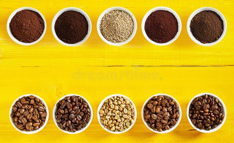 Double border of roasted beans and ground coffee. Double border of a selection of different raw and roasted beans and ground coffee in separate bowls arranged royalty free stock image