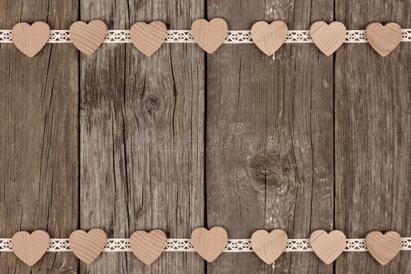 Double border of wooden hearts and ribbon lace over wood. Double border of wooden hearts and ribbon lace over a rustic wooden background royalty free stock photo