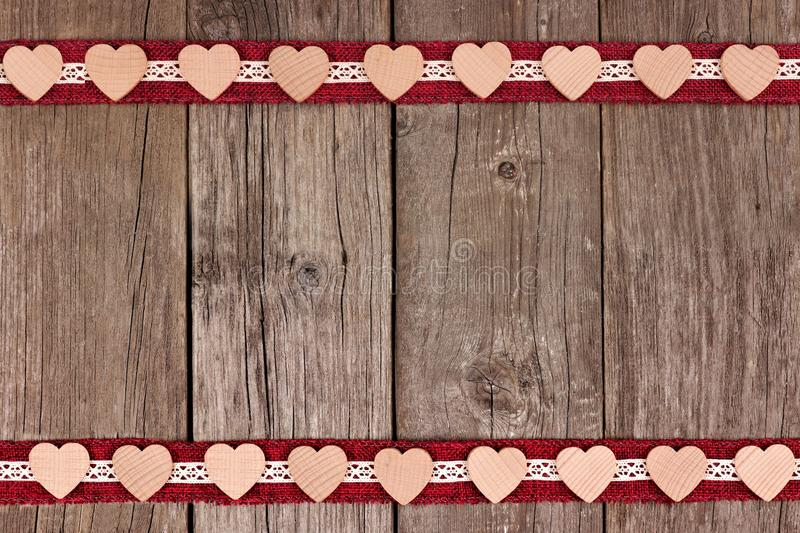 Double border of wooden hearts and ribbon over rustic wood. Double border of wooden hearts and ribbon over a rustic wooden background stock images