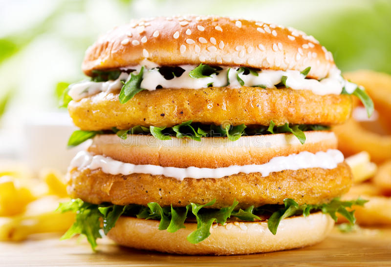 Double burger with chicken. On wooden table stock photos