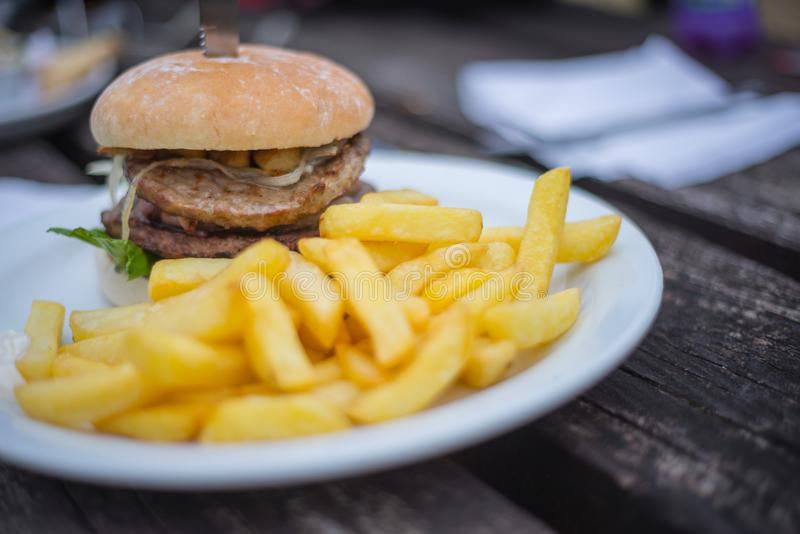 Perfect pub lunch. Double burger and chips at the local pub royalty free stock images