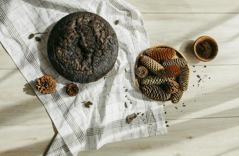 Double chocolate cake and tasty cocoa powder decorated with a checkered tablecloth and pine cones on wooden background. royalty free stock photography