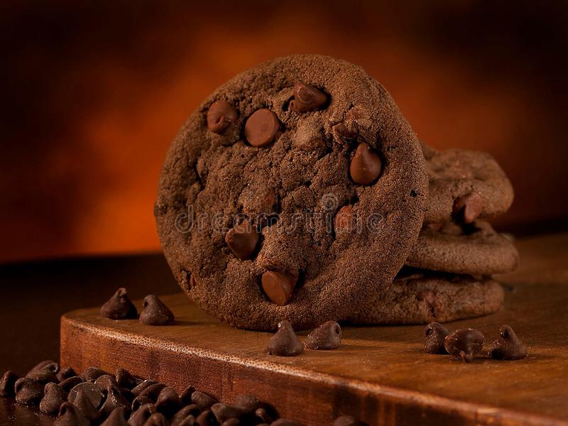 Double chocolate cookies. On a wooden board with chocolate chips in the front royalty free stock photo