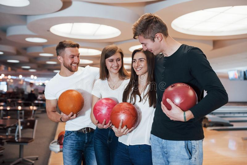 Double date. Young cheerful friends have fun in bowling club at their weekends royalty free stock image