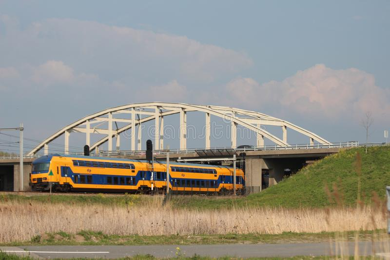 Double decker intercity train at the Moordrecht crossing heading to Den Haag in the Netherlands. stock photo