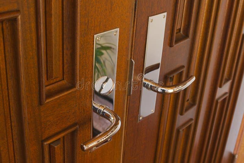 Double door handles. Double chrome door handles on twin mahogany doors in foyer royalty free stock photography