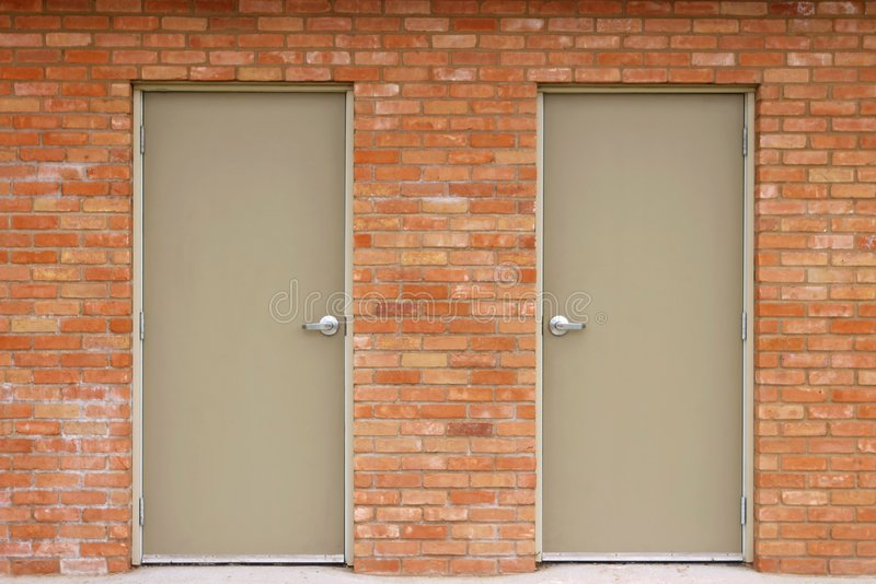 Double Doors and Brick Wall. Abstract view of a set of doors built into a red brick wall stock images