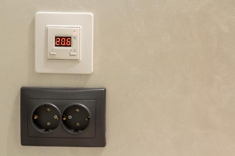 Double electric isolated socket and thermostat installed on light yellow plastered wall. Power supply and temperature regulation, royalty free stock image